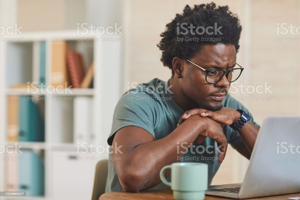 African young man using laptop at home African young man in eyeglasses sitting at the table in front of laptop computer and looking at monitor at home Adult Stock Photo