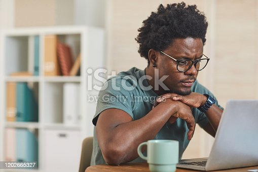 African young man in eyeglasses sitting at the table in front of laptop computer and looking at monitor at home