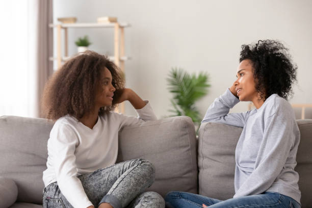 African young mom listening teen daughter sitting on couch together Young african black mother chatting with teen daughter, older sister or friendly nanny and adolescent girl talking sitting together on sofa at home. Good relations different aged people trust concept parent stock pictures, royalty-free photos & images