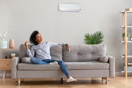African american relaxed woman sitting on comfortable couch in living room at modern home holds air conditioner remote control enjoying breathing fresh cool air at summer or warm air at winter season