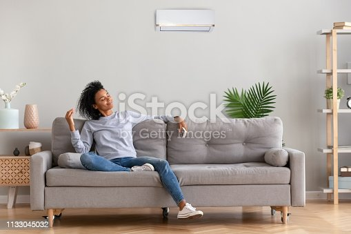 istock African young relaxed woman sitting on couch breathing fresh air 1133045032