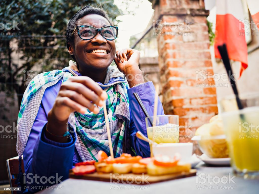 African young woman having appetizer in sidewalk cafe stock photo