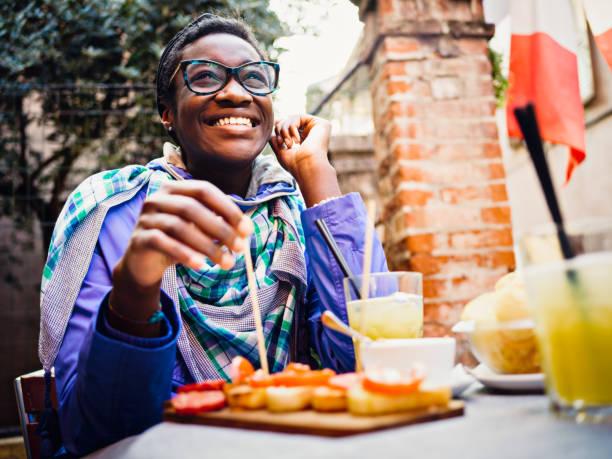 Jeune africaine ayant apéritif en terrasse de café - Photo
