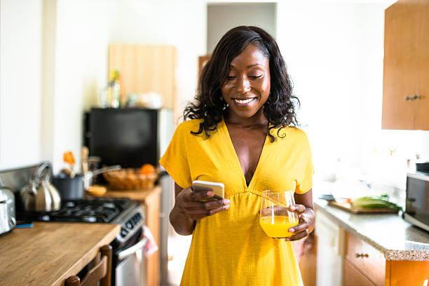 afrikanische lächelnde junge frau trinkt orangensaft - checking stock-fotos und bilder