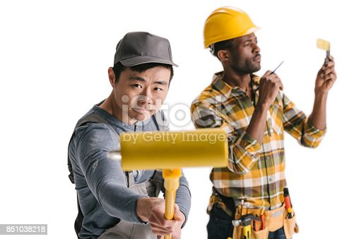 istock african-american and asian construction workers with tools 851038218