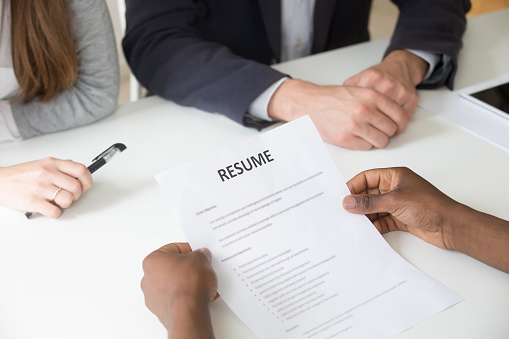 istock African-american applicant holding resume at job interview, close up view 953226924