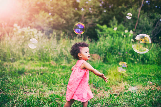 African-American baby girl playing with soap bubbles in the park stock photo