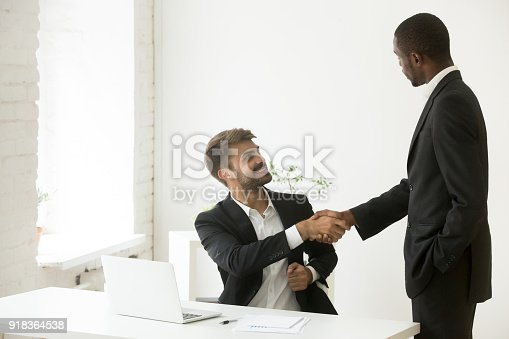 istock African-american boss congratulating caucasian employee with promotion achievement shaking hands 918364538