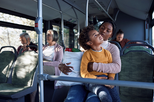African-american little boy and mother holding groceries on public bus