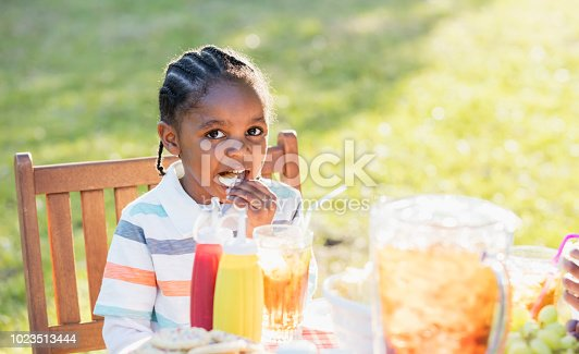 A 3 year old African-American boy sitting outdoors at a picnic table, eating potato chips on a bright, sunny day.