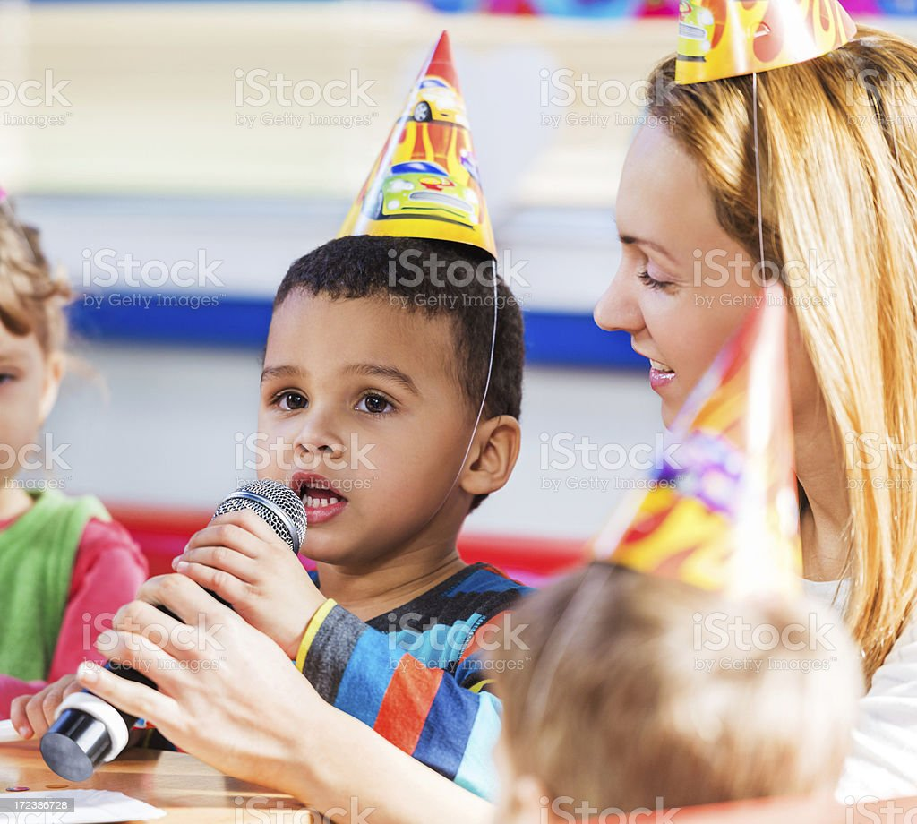 African-American boy singing at birthday party. royalty-free stock photo