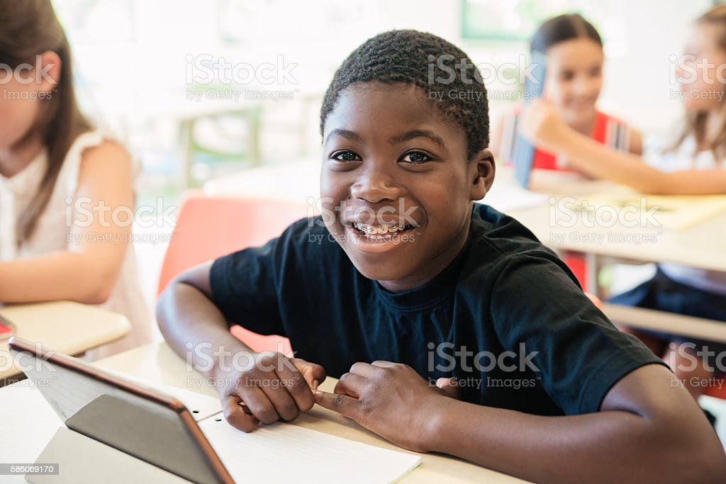 African-american boy using electronic tablet in classroom. стоковое фото