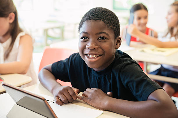 African-american boy using electronic tablet in classroom. stock photo
