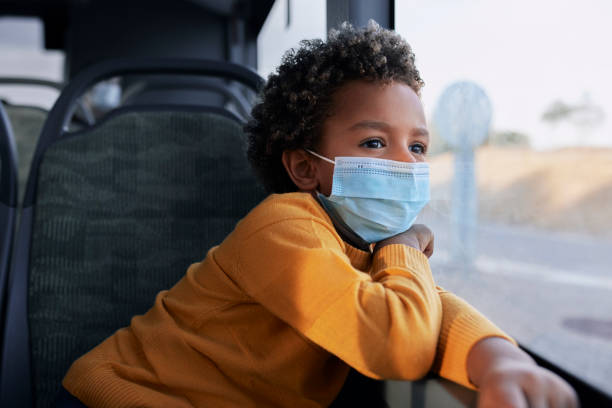 African-american boy with covid mask looking out of window inside bus stock photo