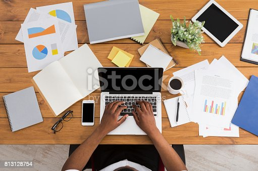 istock African-american businessman at work, table top view 813128754