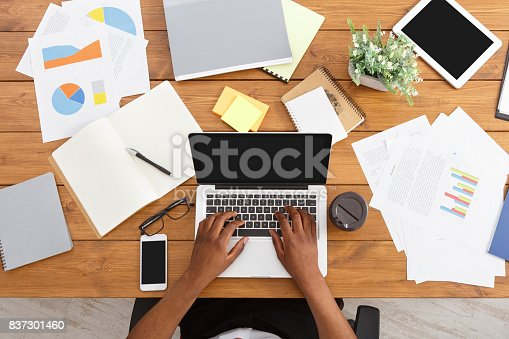 istock African-american businessman at work, table top view 837301460