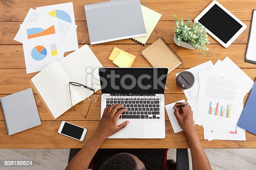 istock African-american businessman at work, table top view 838189524