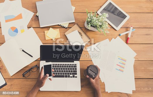 istock African-american businessman at work, table top view 854345498