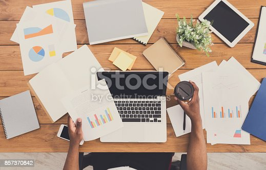 istock African-american businessman at work, table top view 857370842