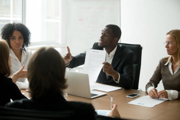 African-american businessman disagreeing with contract terms at group multi-ethnic negotiations stock photo