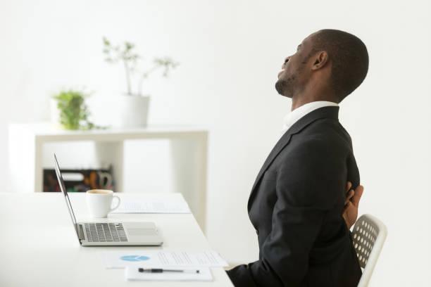 afrikanisch-amerikanischer geschäftsmann gefühl plötzlicher rückenschmerzen sitzen auf stuhl am arbeitsplatz - chiropraktik wellness stock-fotos und bilder