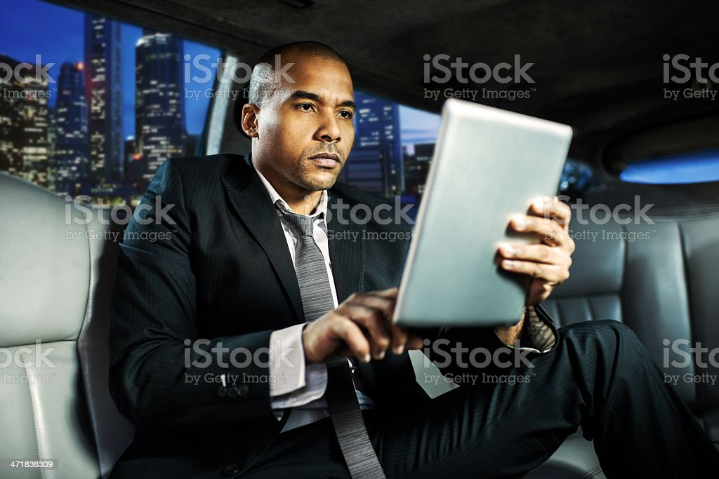 African-American businessman in limousine working on digital tab stock photo