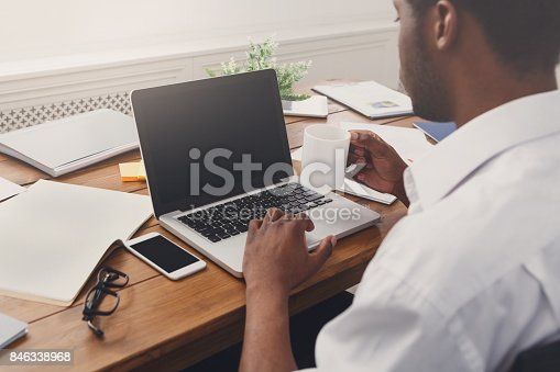 istock African-american businessman in office type on laptop 846338968