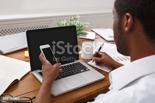 istock African-american businessman in office with mobile and laptop 838189602
