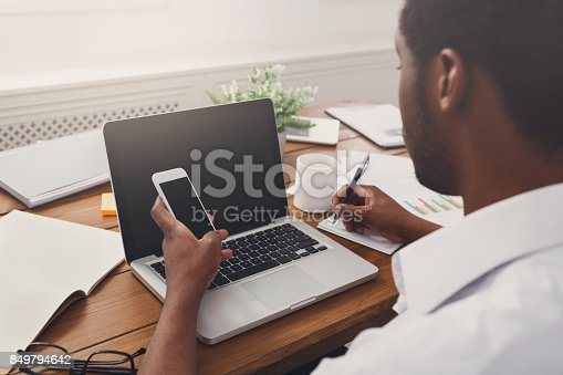 istock African-american businessman in office with mobile and laptop 849794642