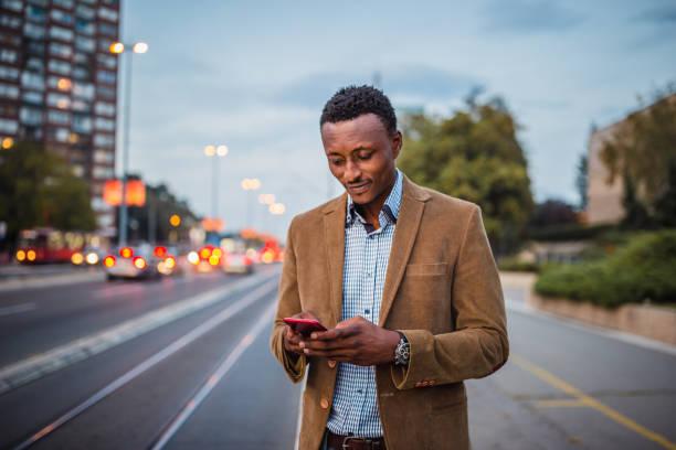 Afroamerikanischer Geschäftsmann auf Geschäftsreise mit dem Handy – Foto