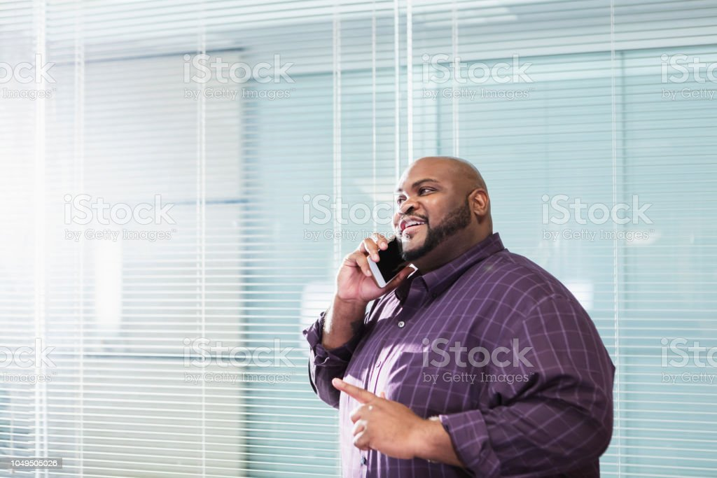 A mature African-American businessman in his 40s standing in an...