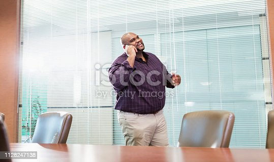 istock African-American businessman with large build on phone 1128247138