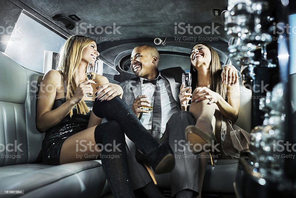 African-American businessman with young women in a limousine. stock photo