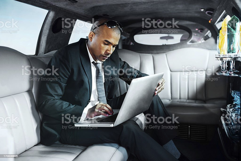 African-American businessman working on laptop in limousine. stock photo