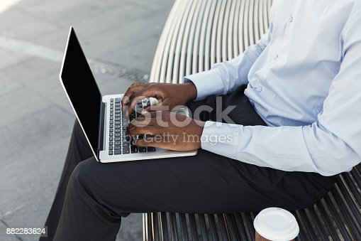 istock African-american businessman working with laptop outdoors 882283624