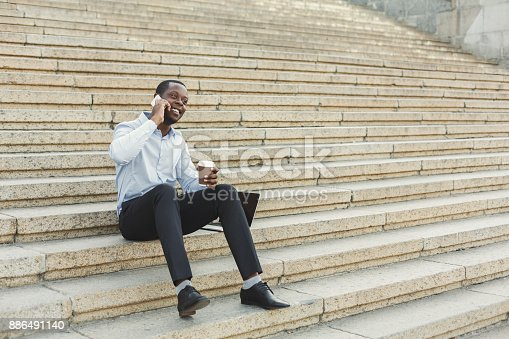 istock African-american businessman working with laptop outdoors 886491140