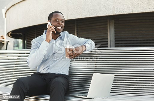 istock African-american businessman working with laptop outdoors 886493398