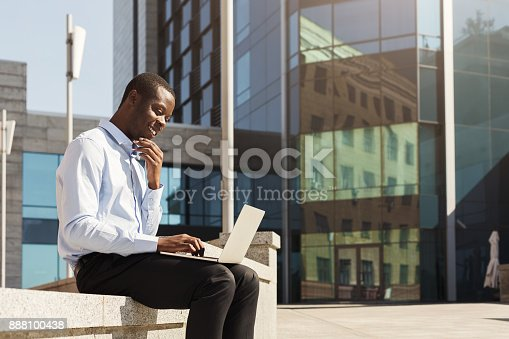 istock African-american businessman working with laptop outdoors 888100438