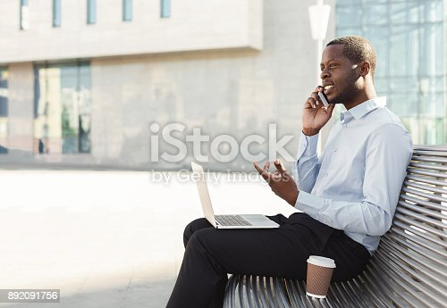 istock African-american businessman working with laptop outdoors 892091756