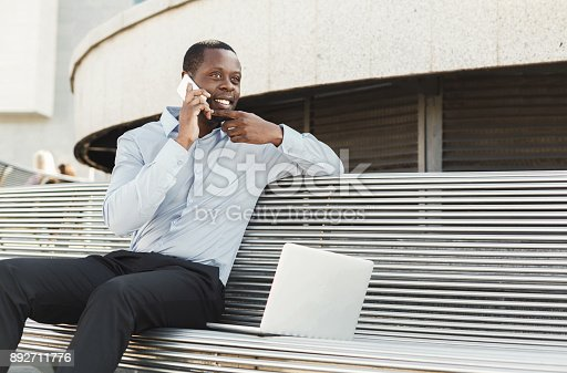istock African-american businessman working with laptop outdoors 892711776