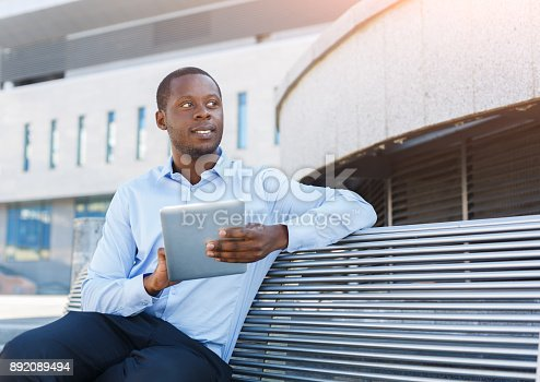 istock African-american businessman working with tablet outdoors 892089494