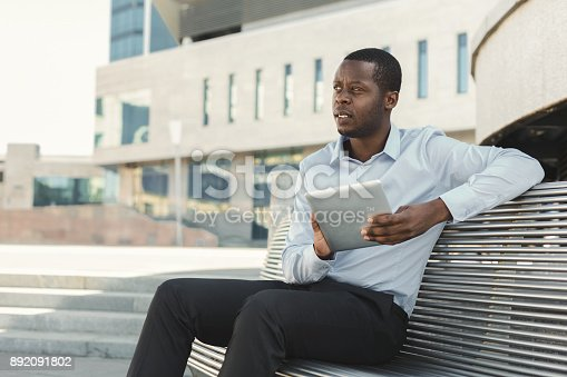 istock African-american businessman working with tablet outdoors 892091802
