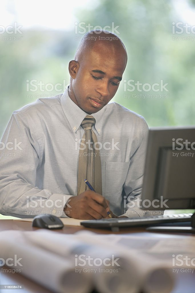 African-American Businessman Writing At Desk royalty-free stock photo
