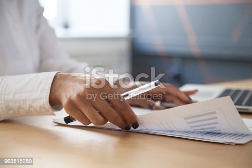 istock African-american businesswoman analyzing statistics report working with graphs, closeup view 963815280