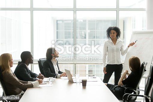 African american businesswoman giving presentation to executive team in meeting room, black business coach or employee working with flipchart reporting about work result, explaining new project idea