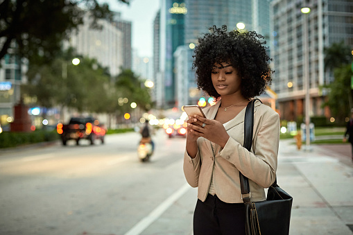 Young female corporate executive standing at curb of busy street checking smart phone as she waits for crowdsourcing taxi at dusk.