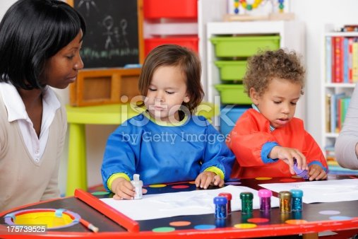 istock African-American Carer/ Teacher Supervising Little Boys During Art And Craft 175739525