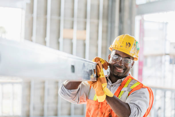 African-American construction worker carrying metal beam A mid adult African-American man in his 30s wearing a hard hat, protective goggles, a safety vest and work gloves, carrying a piece of construction material into the structure being built. The construction worker is smiling, looking at the camera. construction worker stock pictures, royalty-free photos & images