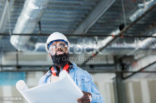 A construction worker wearing a hard hat and safety glasses at an indoor construction site, looking at floor plans. He is a mature African-American man in his 40s with a thick beard. The structure being built is an office building.