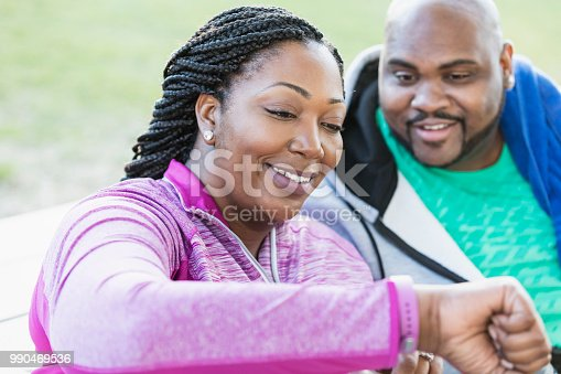 istock African-American couple, checking fitness tracker 990469536